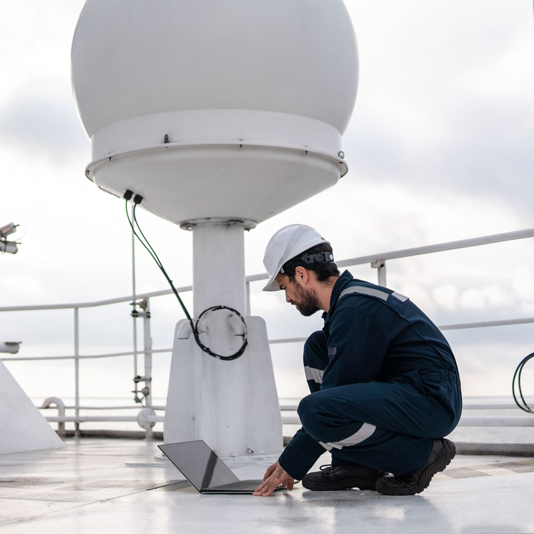 Azimuth Technologies marine service technician near vsat terminal on deck of ship he is working